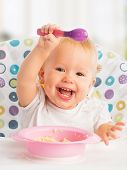 stock photo of spoon  - cheerful happy baby child eats itself with a spoon - JPG