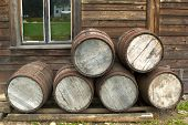 Wooden Barrells Piled Up In Front Of Pioneer Wood Log Cabin Xix Century