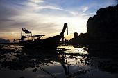 Beatiful sunset with longtail boat silhouette in Railay beach, Krabi