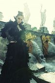 stock photo of evil queen  - Fashion model posing next fountain in summer park - JPG