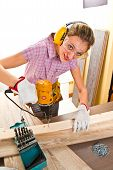 stock photo of hand drill  - Female carpenter at work using hand drilling machine - JPG