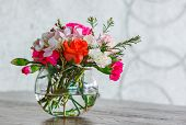 picture of carnations  - Close up rose and carnation flower bouquet in glass vase on wooden table - JPG
