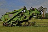 stock photo of threshing  - A old green threshing machine  is parked in a field - JPG