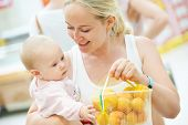 woman choosing apricot with child during shopping at fruit vegetable supermarket