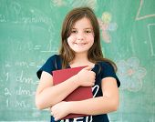 Schoolgirl on school board with book posing