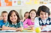 Cheerful kids sitting with apple on desk in classroom