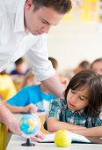 Cheerful teacher with kids learning in school classroom