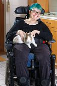 picture of caress  - Young woman with infantile cerebral palsy due to birth complications confined to a multifunctional wheelchair caressing a pygmy rabbit as part of her therapy giving the camera a charming smile - JPG