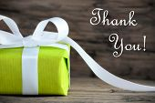 stock photo of give thanks  - Green Gift with White Ribbon on Wood and the Text Thank You - JPG