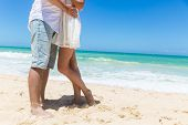 Romantic Couple Holding Hands On The Beach.