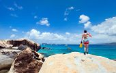 Young woman with snorkeling equipment enjoying view of a tropical beach standing on granite boulder