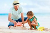 Father and daughter on beach playing and building sand castle