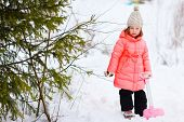 Adorable little girl outdoors on beautiful winter day playing with snow