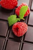 dark chocolate bar with raspberry as background