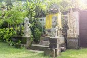 Bali Temple with Three Statues On Lush Green Garden
