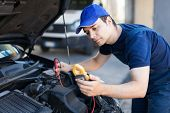 Auto electrician troubleshooting a car engine