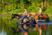 Two young men astride horses go down the river