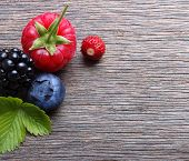 Summer berry fruits. Berries. Raspberry, Strawberry, Blueberry, Blackberry on wooden background.