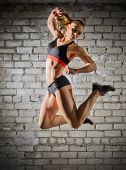 Muscular woman on grey brick wall (normal version)