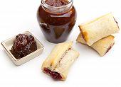 Puff bun with jam and jar of plum jam