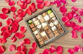 Box Of Tasty Chocolates Among Rose Petals - A Romantic Gift