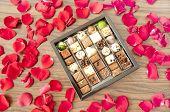 Box Of Tasty Chocolates Among Rose Petals - A Romantic Gift