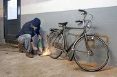 stock photo of dynamo  - Bicycle thief busy breaking the lock with a portable grinding machine - JPG
