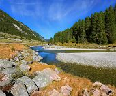 Autumn creek shallow. Austrian Alps. The narrow stream flows between fields and forests