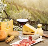 Red Wine Glass With Chesse Selection Against  Italian Collio Vineyards