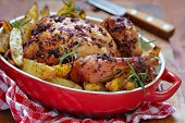 stock photo of baked potato  - Whole roasted chicken with potatoes in red baked dish