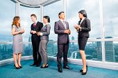 Businesspeople standing and talking in front of office window