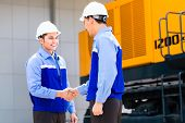 Asian engineer having agreement handshake at construction machinery of construction site or mining c