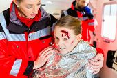stock photo of accident victim  - Emergency doctor and paramedic or ambulance team helping accident victim - JPG