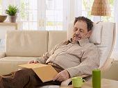 Senior man sleeping in armchair at home.