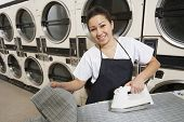 Portrait of a happy woman wearing apron ironing in front of washing machines