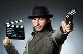 Man with gun and movie clapboard