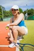 Pretty tennis player smiling on court on a sunny day