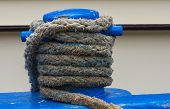 picture of bollard  - Blue Bollard on ship with white dirty rope - JPG