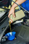 auto mechanic technician replacing and pouring motor oil into automobile engine at maintenance repai