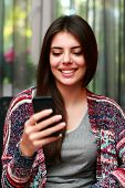 Happy attractive woman using smartphone at home