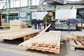 pic of manufacturing  - Worker of wood processing manufacture operating on woodworking machine - JPG