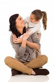 playful young girl hugging mother isolated on white