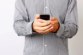 Closeup portrait of a male hands using smartphone