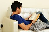 Young man reading a book while relaxing on sofa at home