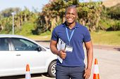 handsome african american driving instructor holding clipboard in testing ground
