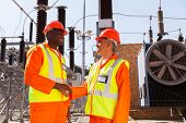 smiling technicians meeting in electrical substation
