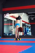 Redhead muscled female athlete does handstand