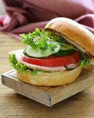 snack burger with fresh vegetables and ham on a wooden board