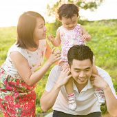 Portrait of happy Asian family playing piggyback at outdoor park during summer sunset.