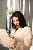 Постер, плакат: surprised businesswoman reading journal